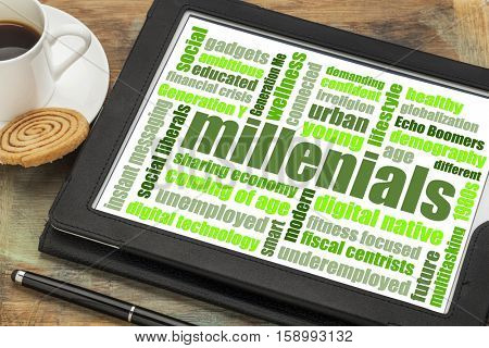 millenials word cloud on a digital tablet with a cup of coffee - demography concept