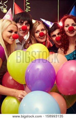 Happy group of young people in clown s noses holding balloons and smiling at camera
