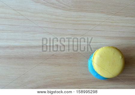 Yellow And Blue French Macaron Cookies On Wooden Board