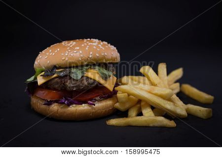 Burger and French fries. black background. fastfood.