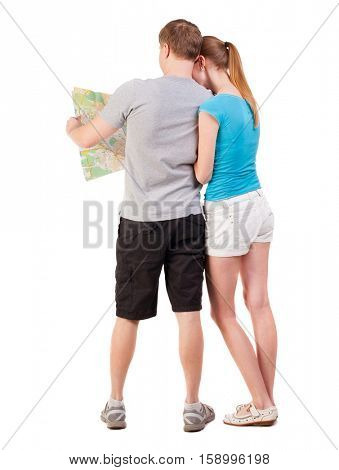 Back view journey of the young couple looking at the map. Rear view people collection.   Isolated over white background. a young couple on a journey in search for the right route map