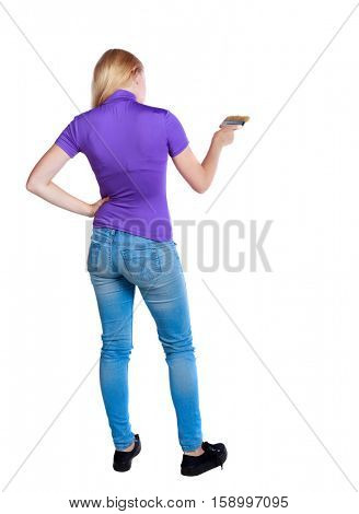 Back view of a girl who paints the paint roller. rear view people collection. backside view of person. Isolated over white background. Long-haired blonde in the purple shirt color brush.