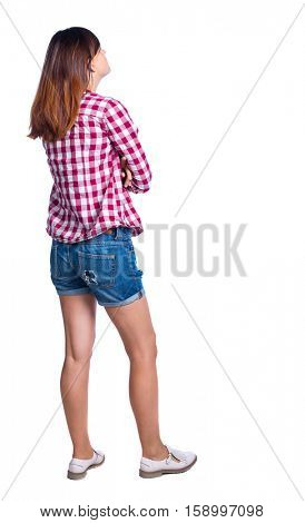 back view of standing young beautiful  woman.  girl  watching. Rear view people collection.  backside view of person.  Girl in shorts and a plaid shirt looking sideways with his arms crossed.