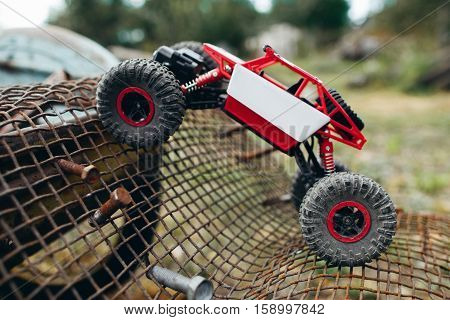 Toy truck overcoming grille with screws profile. Side view on rc crawler riding on metal lattice, free space.
