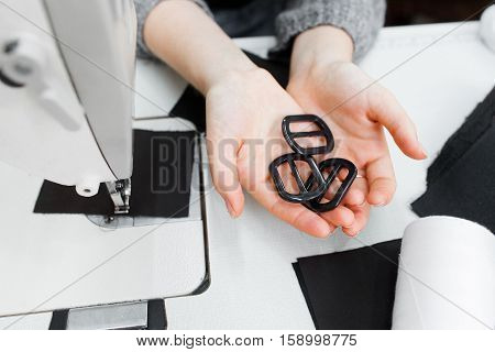 Designer hands with black buckles top view. Female tailor hands holding findings. Garment industry, tailor workshop, clothes making concept