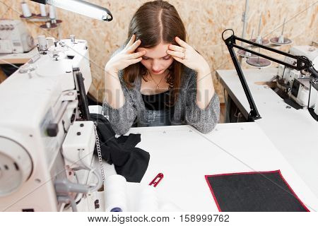 Seamstress realized she made mistake, copy space. Tired frustrated tailor sitting in stress, touching her head in despair. Troubles at work, failure, misfortune concept