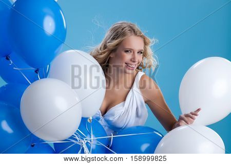 Young attractive blonde woman holding a bunch of air balloons in her hand