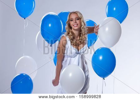 Young attractive blonde woman holding a bunch of balloons in her hand