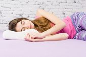 Young blonde Caucasian woman in pajamas sleeping on ergonomic shaped pillow at home in her bed. Closeup, no retouch, studio lighting. poster