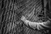 Little girl hand holding fence - Black and white image of a little girl hand grabbing a metal fence depicting drama poster