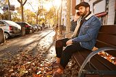 Attractive young man with a beard dressed in denim jacket, black trucker hat and black trousers sitting on a wooden bench in an autumn city street talking on the phone poster