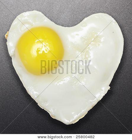 Fried egg like heart on frying pan.