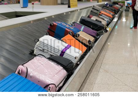 Suitcase Or Luggage With Conveyor Belt In The Airport. Traverler Waiting Suitcase Or Luggage In Arri