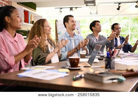 Group Of Businesspersons Cheering And Clapping For A Co-worker At The Office