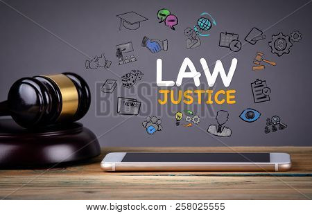 Law And Justice Concept. Mobile Phone On A Wooden Table And A Gray Background