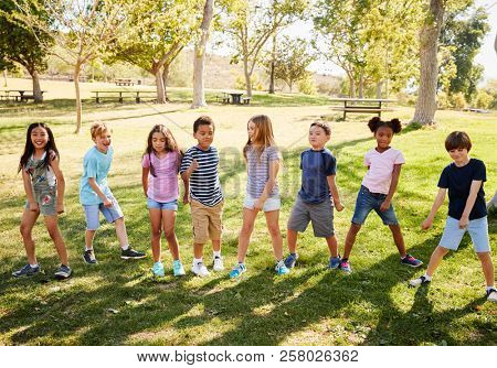 Multi-ethnic group of schoolchildren playing in park poster