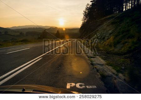 Car Travel In Sunset Landscape. Traveling By Car On The Road. Car In Rural Landscape In Sunset. Trav
