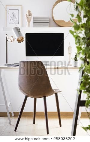 Leather Chair Standing By Wooden Desk With Mockup Monitor, Metal Lamp And Decor In Real Photo Of Hom