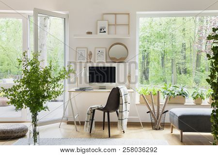 Real Photo Of White Living Room Interior With Big Window, Glass Door, Fresh Plants, Wooden Desk With