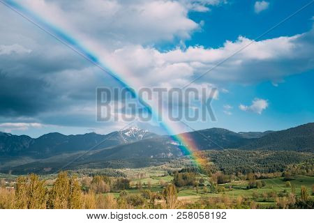 Catalonia, Spain. Pyrenees Mountains Landscape With Rainbow Above Spring Forest And Hills. Spanish S