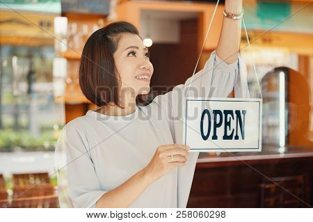 Happy Vietnamese Young Woman Hanging Open Sign On Door On Her Pub