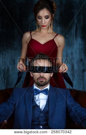 Couple In Dating. Woman Female In Expensive Red Evening Dress Tying Woman Eyes.  Rich Man Male Dress