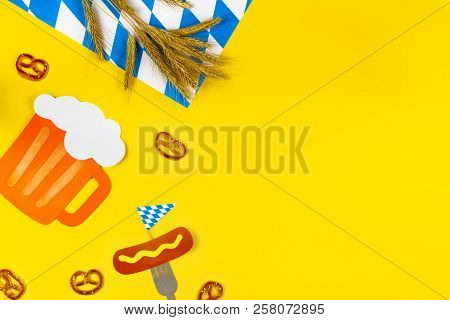 October fest concept. Wheat, germany beer, sweet tasty snacks pretzels and fork with sausage with mustard on yellow background.  Ads event of october beer festival in autumn october month. Beer day poster