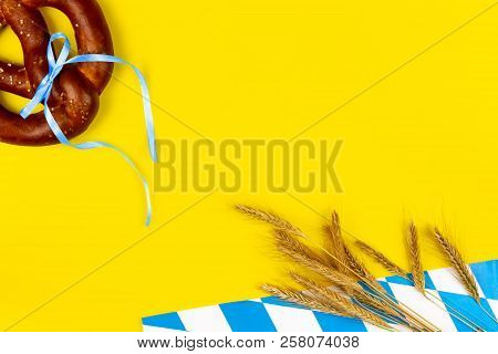 Germany october fest concept. Wheat, sweet tasty bread snack pretzel as snack to germany beer on yellow background.  Ads event of october beer festival in autumn october month poster