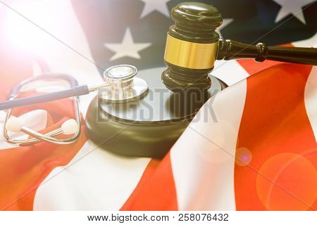 Gavel And Stethoscope On National Flag Of Usa. Forensic Medicine Concept. Judicial Medical Practice,