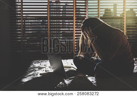 Depressed Women Sitting Head In Hands When Working With Technology Laptop On The Bed In The Dark Bed