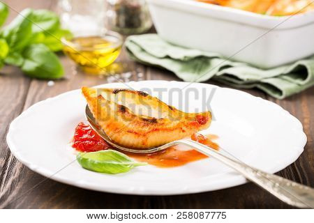 Italian Pasta Conchiglioni Rigati Stuffed With Three Sorts Of Cheese And And Baked In Tomato Sauce.