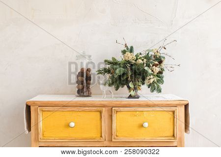 Christmas decorations and conifer twigs placed on dresser with yellow drawers on background of white wall poster