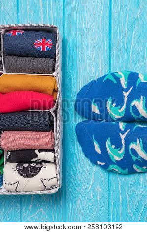 Box With Different Colorful Socks. Feet Selfie And A Socks Organizer On A Blue Background. Top View,