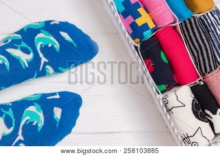 Feet Selfie And A Socks Organizer On A White Wooden Background. Top View