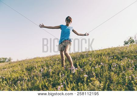 A Girl Is Walking Along The Field. A Woman Walks Through The Meadow, Arms Outstretched. Wildflowers