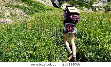 Woman Hiker Climbs Uphill In A Hiking Trip With Beautiful Scenery. Girl With A Backpack On The Climb
