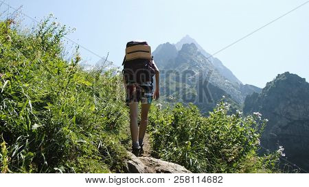 Woman Hiker Climbs Uphill In A Hiking Trip With Beautiful Landscape. Girl With A Backpack On The Cli