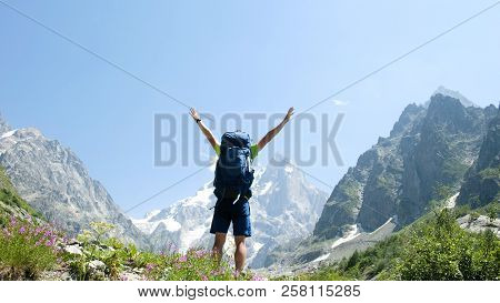 Man Climbs Uphill And Raises His Hands Up After Climbing In A Hiking Trip, A Beautiful View Opens Up