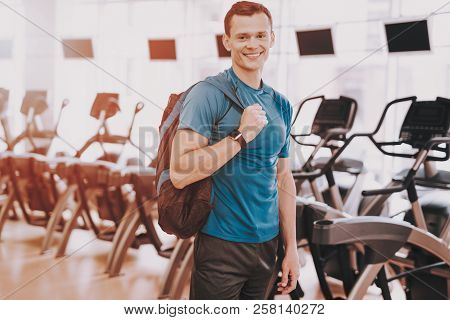 Smiling Young Man In Sport Club Near Treadmills. Healthy Lifestyle Concept. Sport And Training Conce