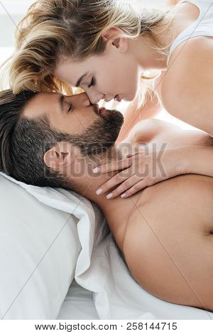 Side View Of Sexy Young Couple Able To Kiss In Bed
