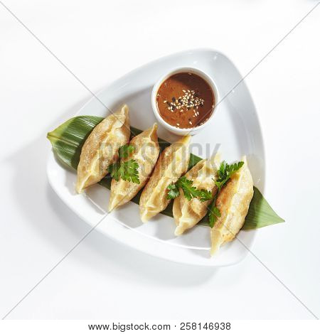 Oriental Fried Dim Sum with Minced Meat also known as Gyoza, Dim Sum, Jiaozi or Momo on a Banana Leaf with Spicy Sauce Top View. Hot Crunchy Deep-Fried Beef and Mutton Dimsum Isolated on White
