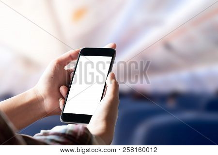 Airplane Passenger Using Smart Phone On Plane. Businessman Touching Blank Screen Mobile Phone At Air