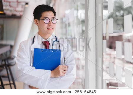 Asian Smart Doctor Standing Arms Crossed And Holding A Blue Document File.