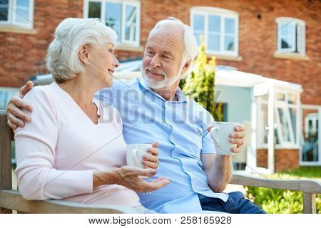 Retired Couple Sitting On Bench With Hot Drink In Assisted Living Facility