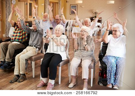 Carer Leading Group Of Seniors In Fitness Class In Retirement Home