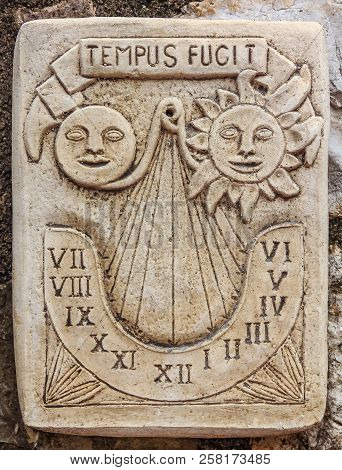 Antique marble sundial clock with a Latin inscription, meaning time flies in  a picturesque medieval city of Eze, France along the Mediterranean Sea poster