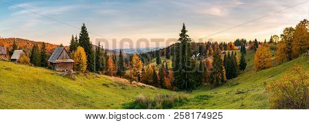 Panorama Of Village In Apuseni Mountains. Beautiful Autumn Landscape At Sunset. Mixed Forest In Red