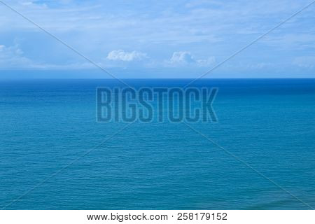 Sea Turquoise Color And Blue Sky With White Clouds.