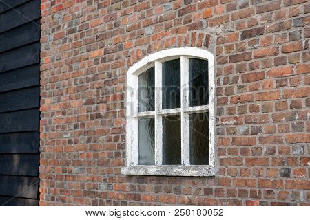 Brick Wall With White Painted Concrete Window In A Restored Dutch Farmhouse. The White Paint Has Par