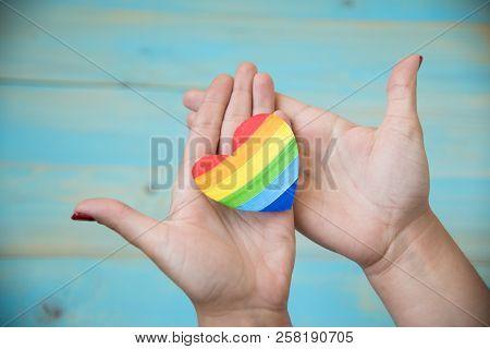Hand On Blue Background Holding Heart Rainbow